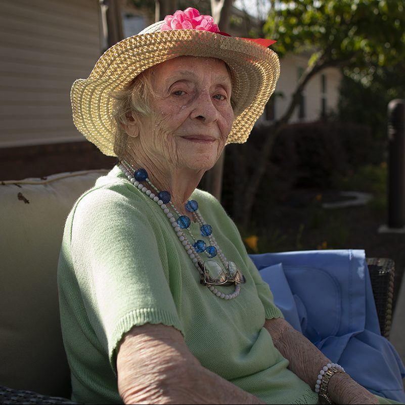 Caucasian resident sitting in the sun with a hat.