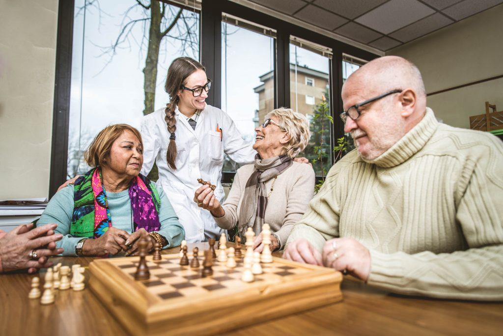 Seniors at an Assisted Living socializing and playing chess.