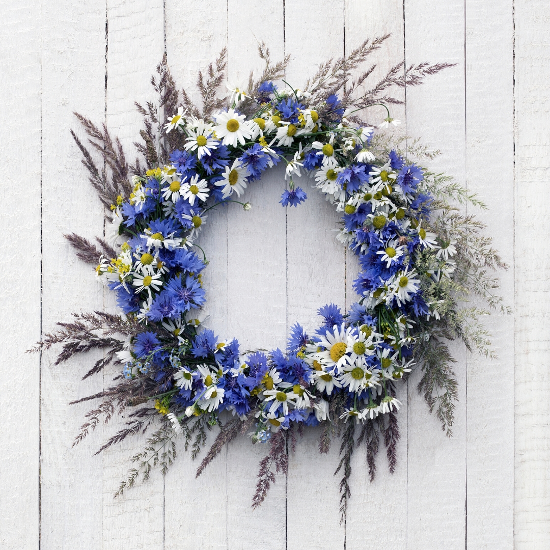 Beautiful wreath with purple and white flowers on door