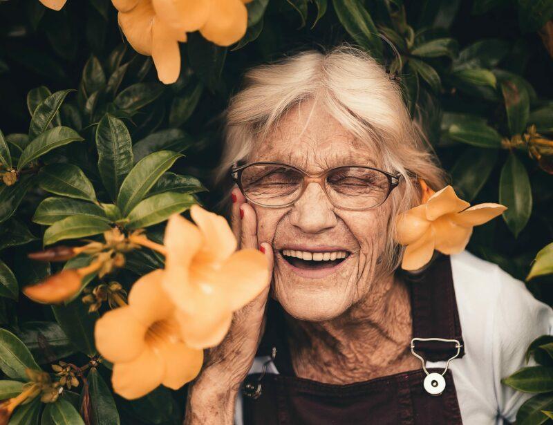 Caucasian woman smiling amid orange flowers