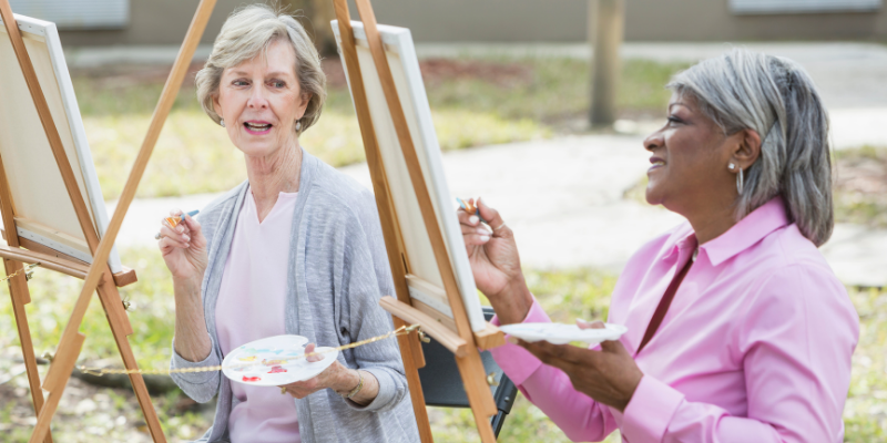 African american woman and caucasian woman painting outdoors at a life enrichment activity in a senior living community.