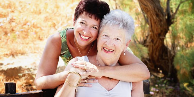 Caucasian mother and daughter smiling for choosing senior living.