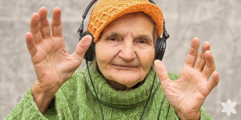 Caucasian senior woman listening to music through headphones.