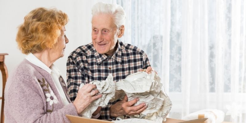 Caucasian elderly couple downsizing from a home to move into a Priority Life Care Assisted Living Community.