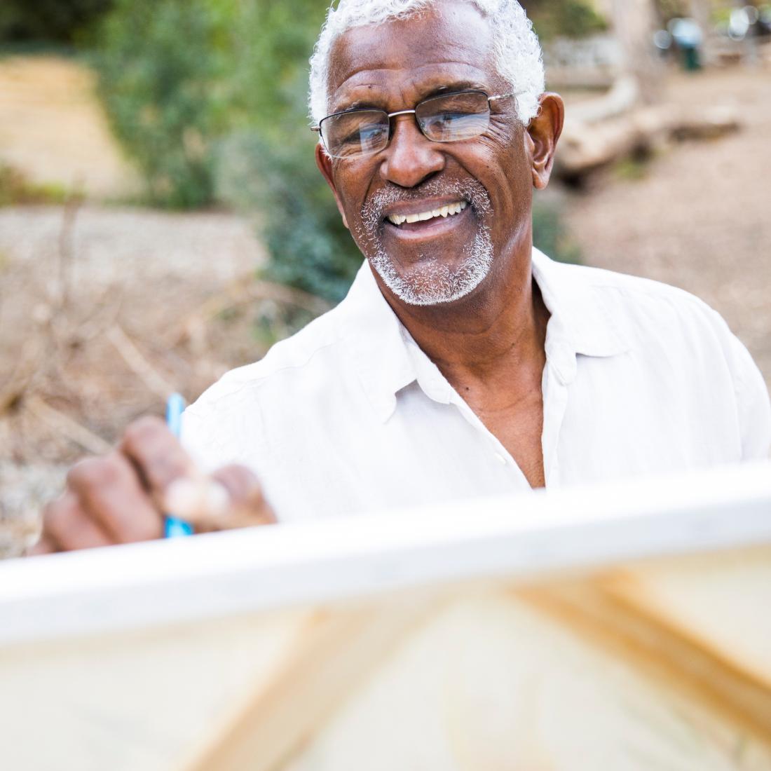 Elderly african american man painting at Valparaiso Senior Village Assisted Living