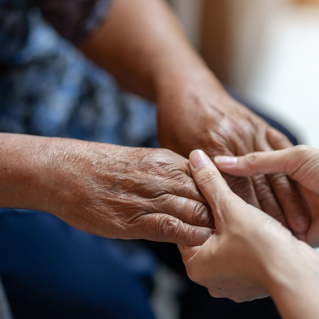 Priority Life Care caregiver holding hands with a resident